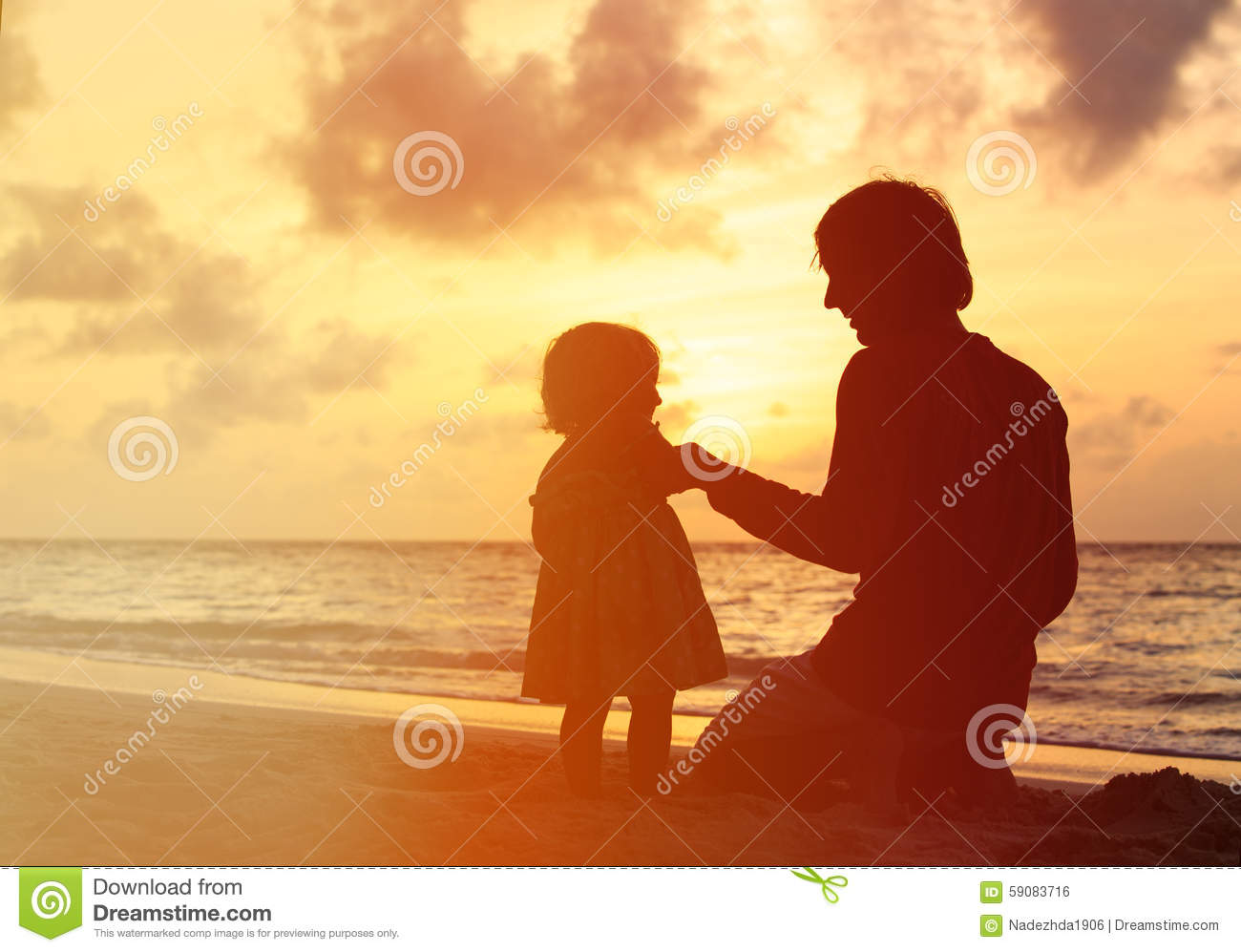 Father And Little Daughter Holding Hands At Sunset Stock Photo