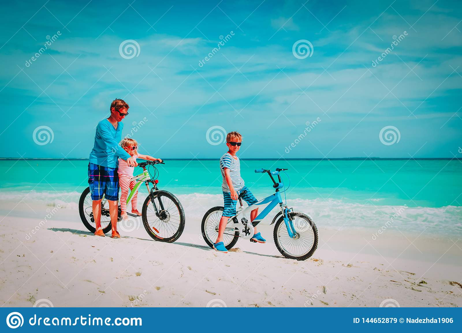 Father with little son and daughter biking on beach