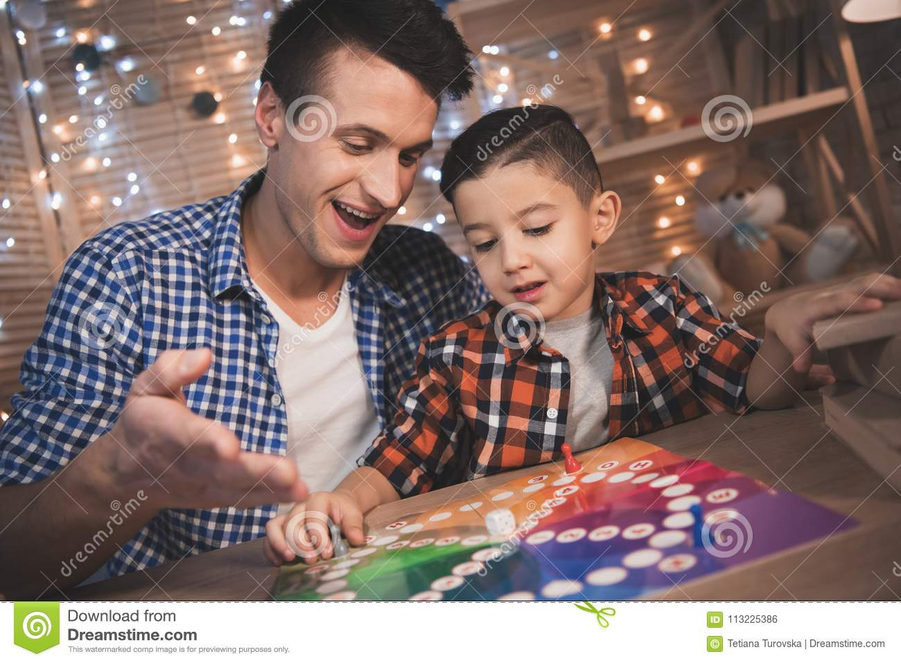 Father and little son are playing board game at night at home.