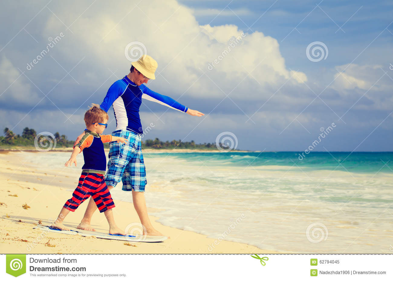 Father and little son practicing surfing positin