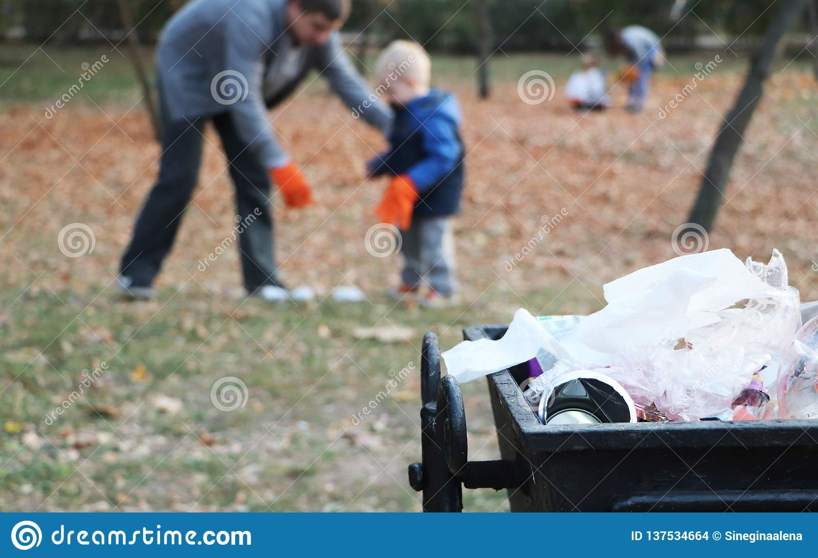 Father and little son scavenging in the park. Background - trash and litter bin. The concept of ecology and protecting the planet