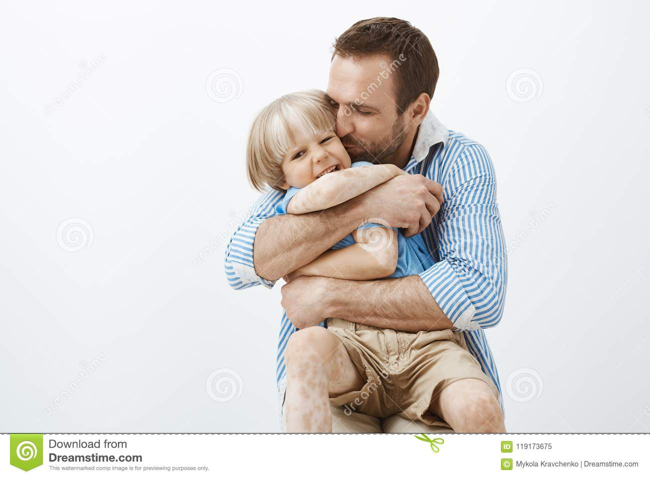 f749e68b Father loves his little son like no one else. Cute good-looking caring dad  hugging and kissing child in cheek, feeling happy spending time with kid,  ...