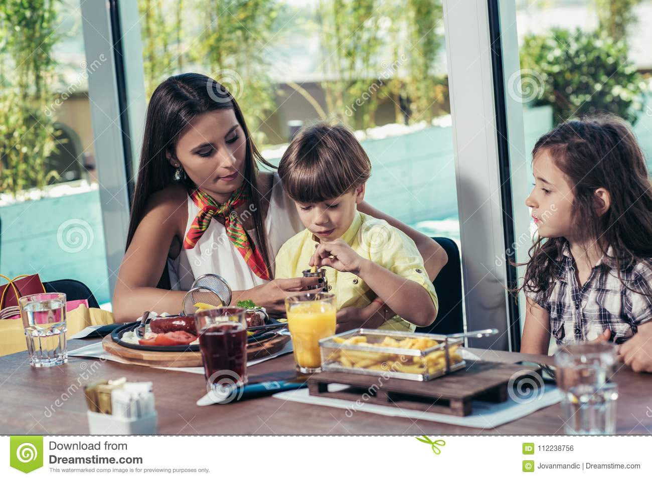 Mother with children enjoying meal in restaurant.