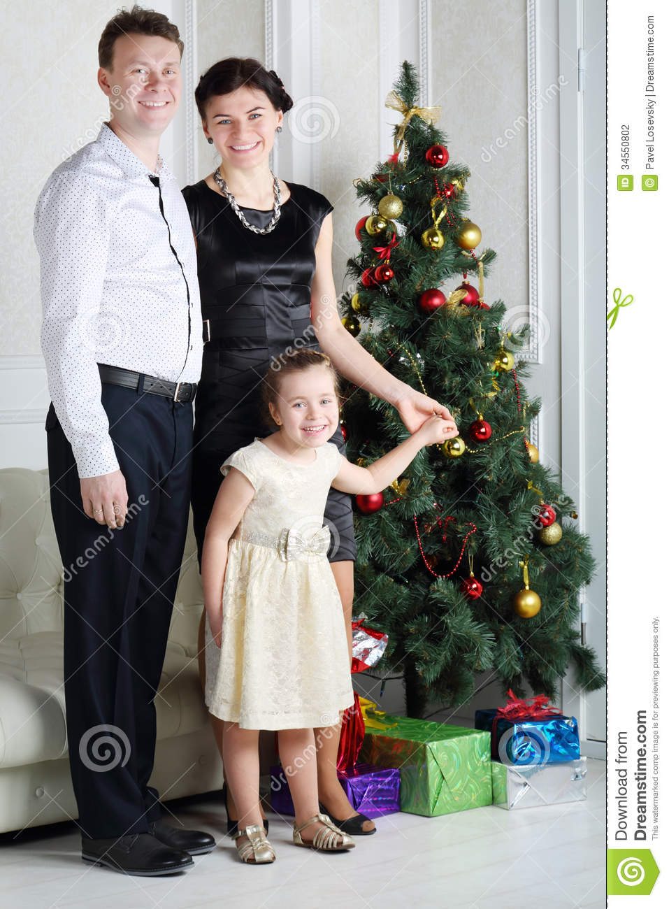 Father Mother And Daughter Stand Near Christmas Tree
