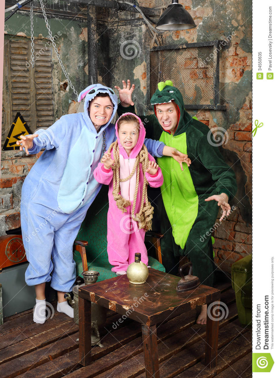 Father Mother And Little Daughter In Costumes Of Dragons