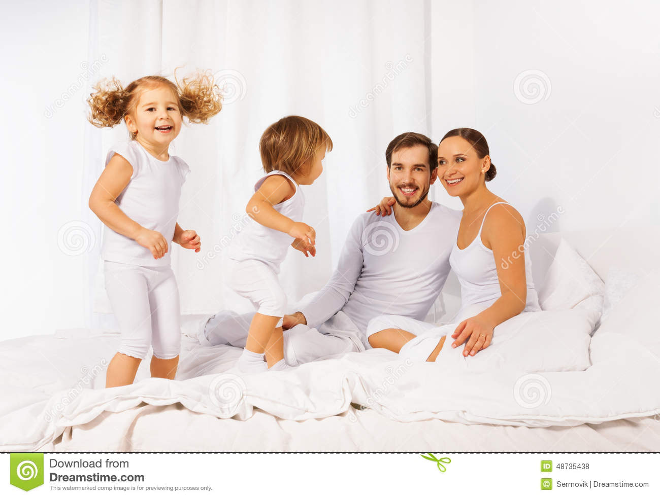 Kids On Bed Father Mother And Their Cute Kids On White Bed Stock Photo .