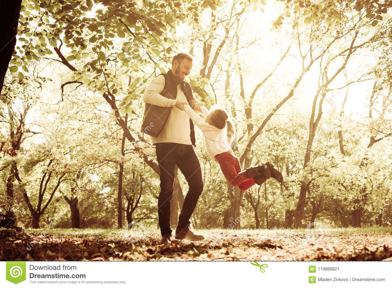 Father in park with daughter holding hands and rotate in