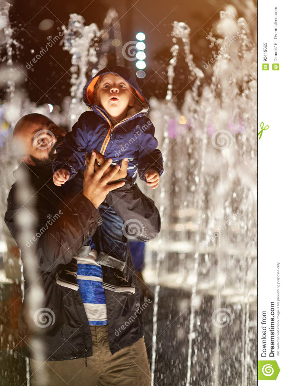 Father play with kid in fountain