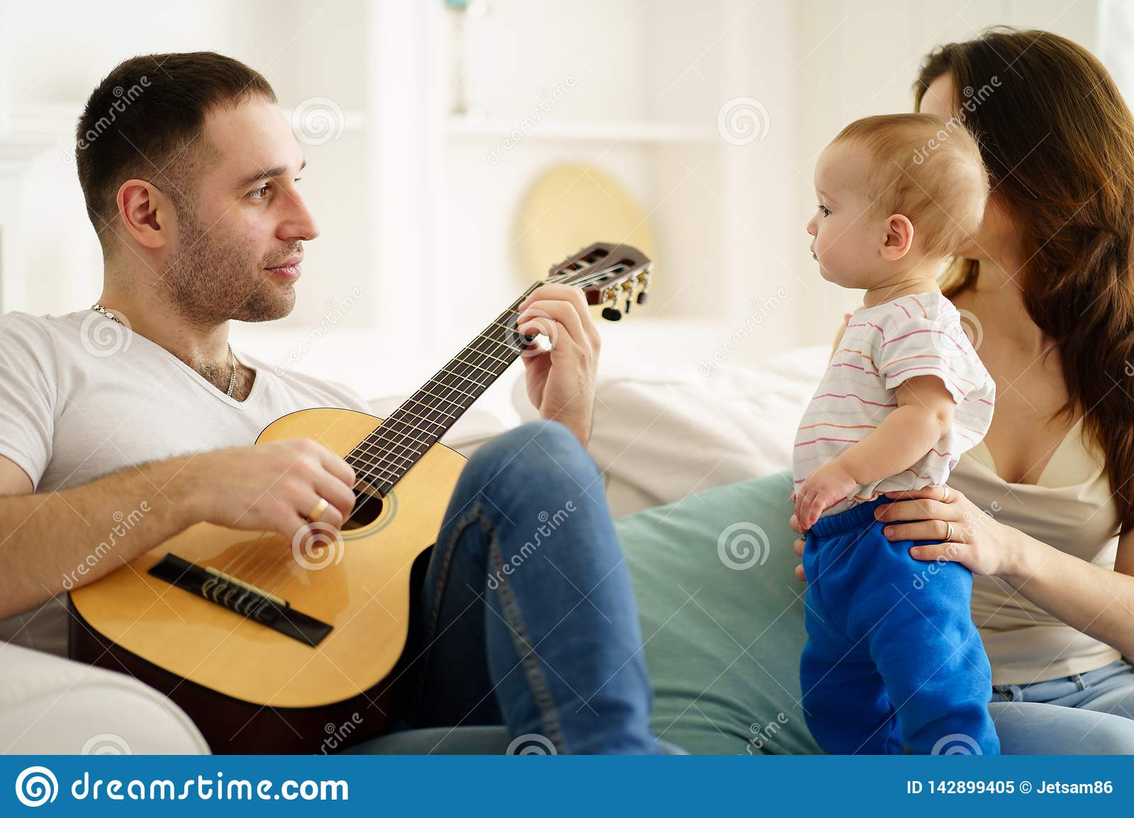 Father Playing Guitar For Mother And Son  Leisure Stock