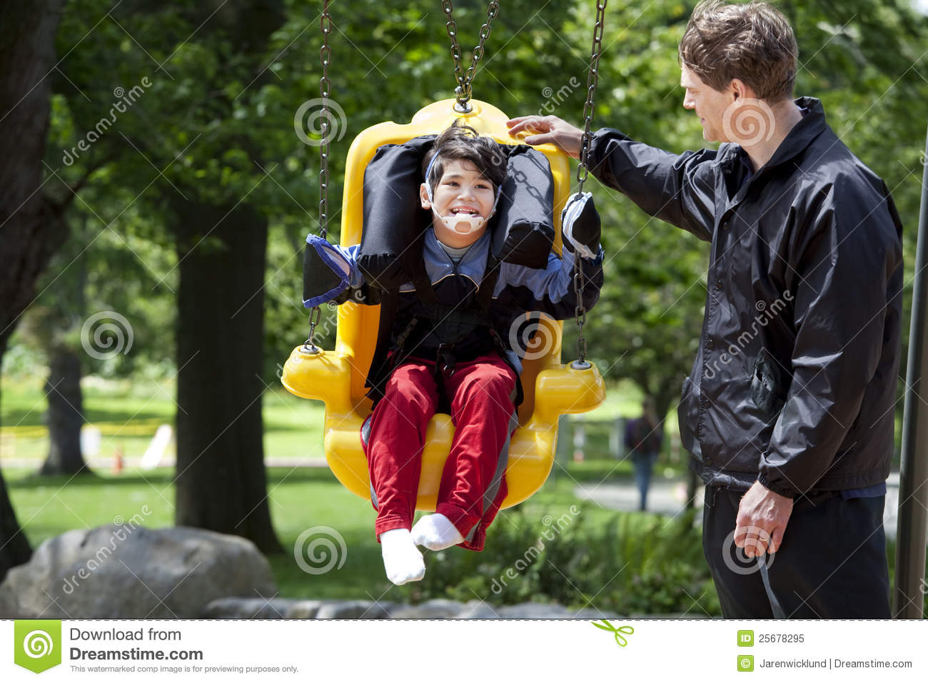 Father Pushing Disabled Boy In Special Needs Swing Royalty