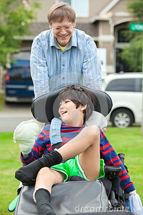 Father Pushing Ten Year Old Disabled Son In Wheelchair