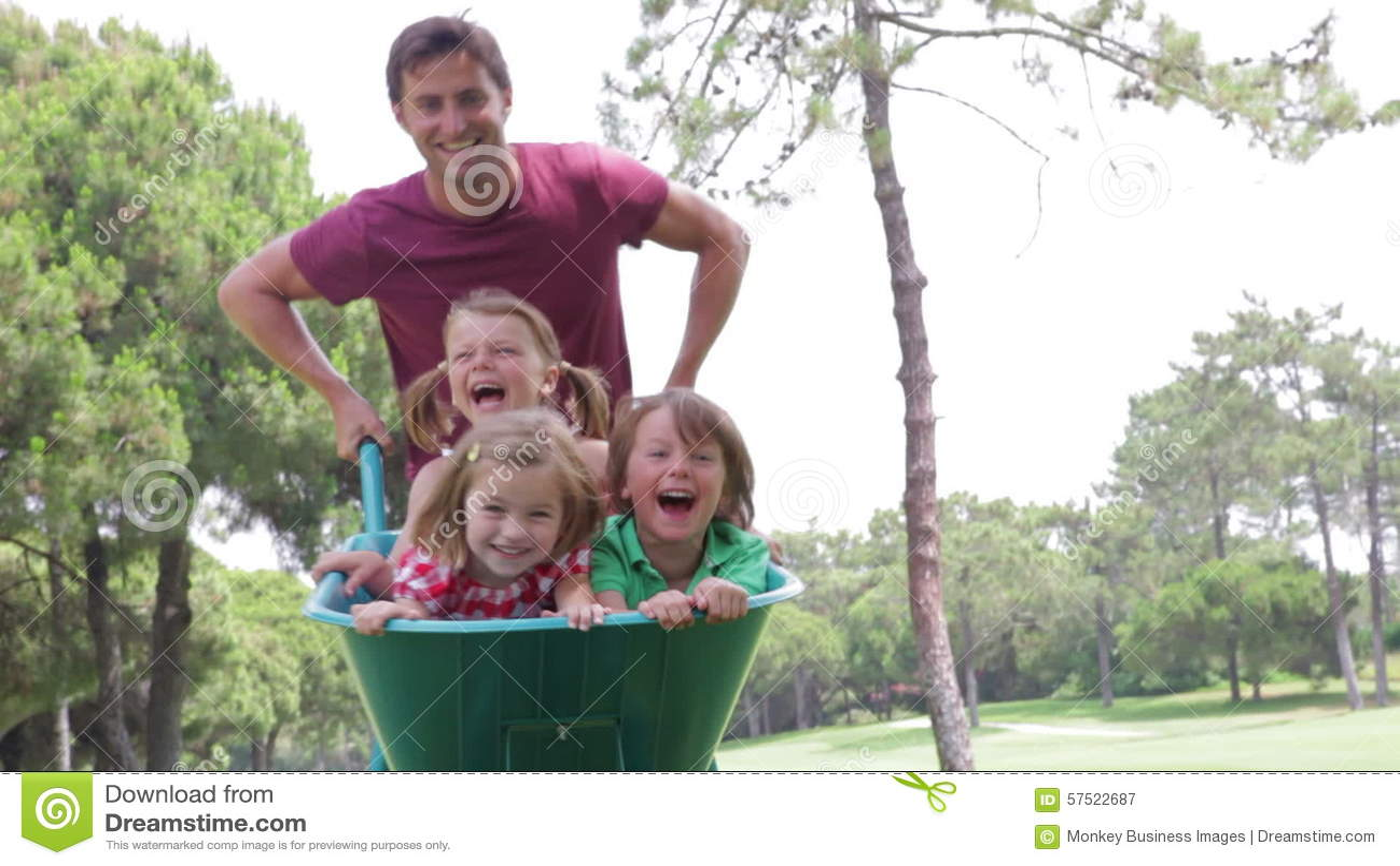 Father Pushing Three Children Sitting In Wheelbarrow