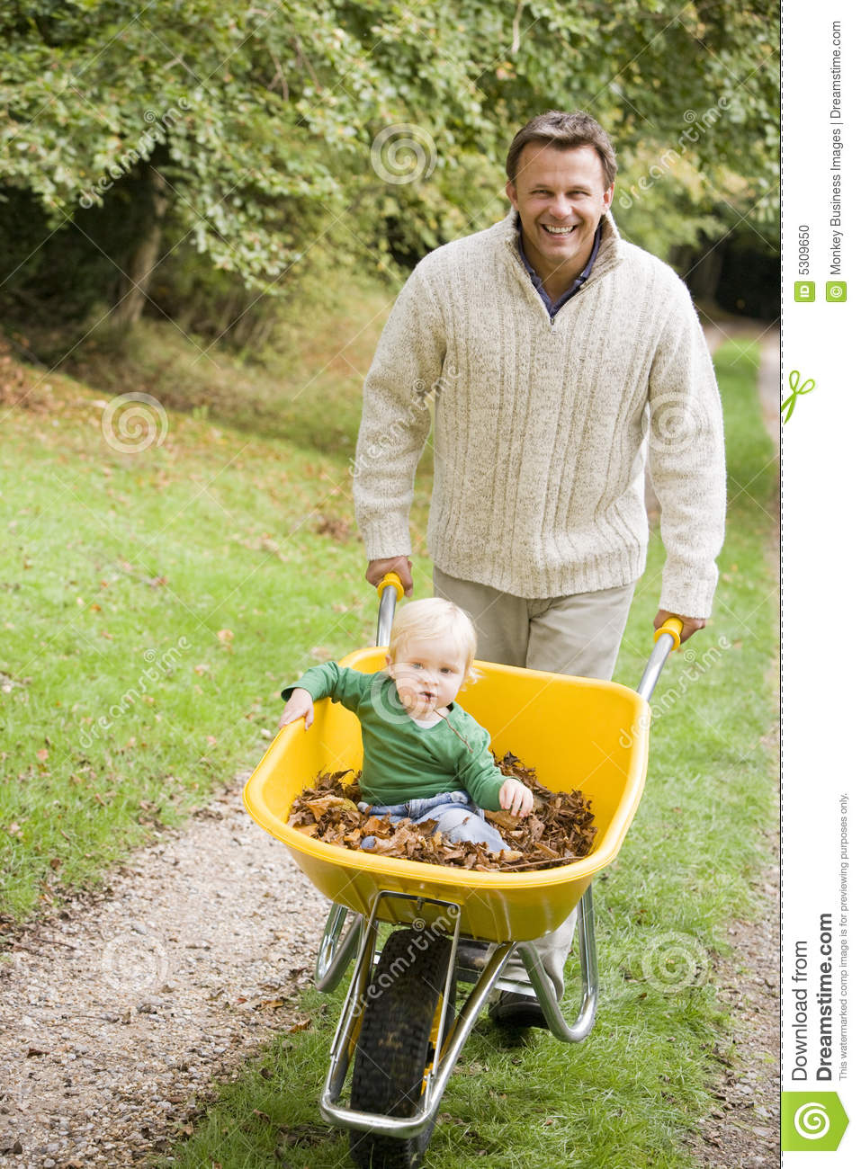 Father Pushing Young Son In Wheelbarrow Stock Photo Image