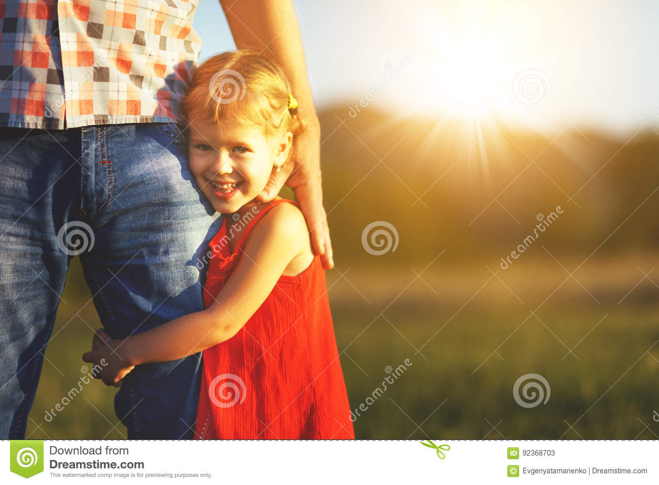 Father`s day. Child girl hugging father in nature at sunset