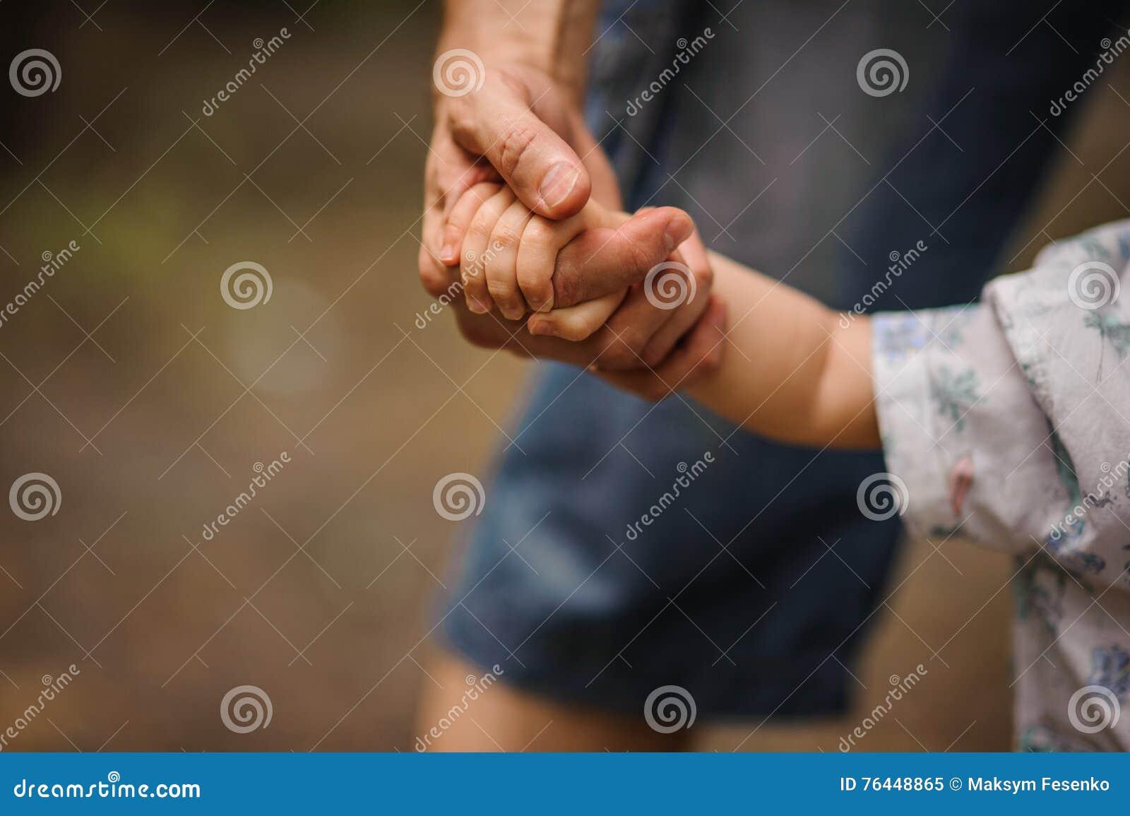 Father& x27; s ręki prowadzenie jego dziecko syn w lato lasowej naturze plenerowej,