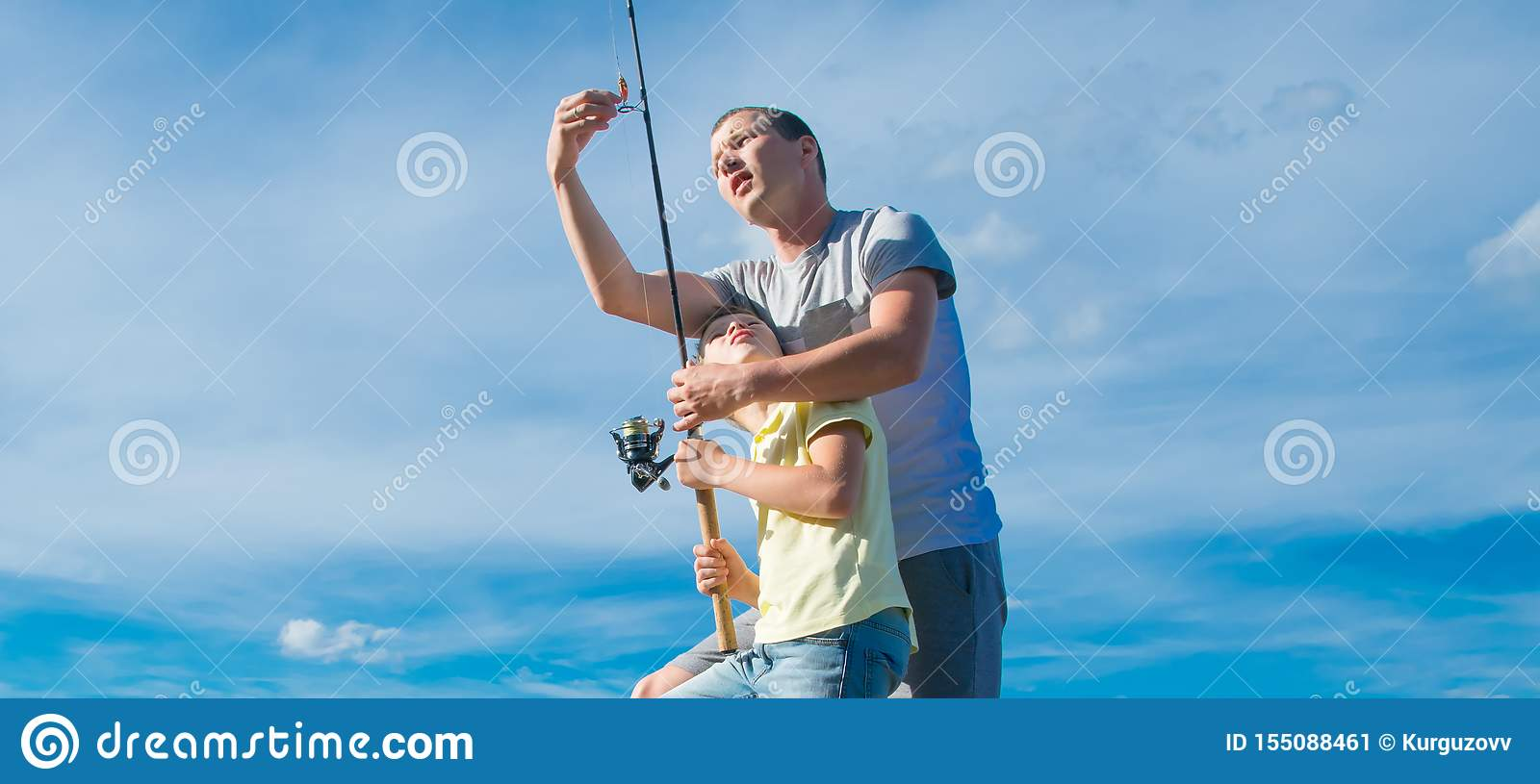 The father shows his son on the pier, how to set up a fishing rod to catch fish, against the blue sky, close-up