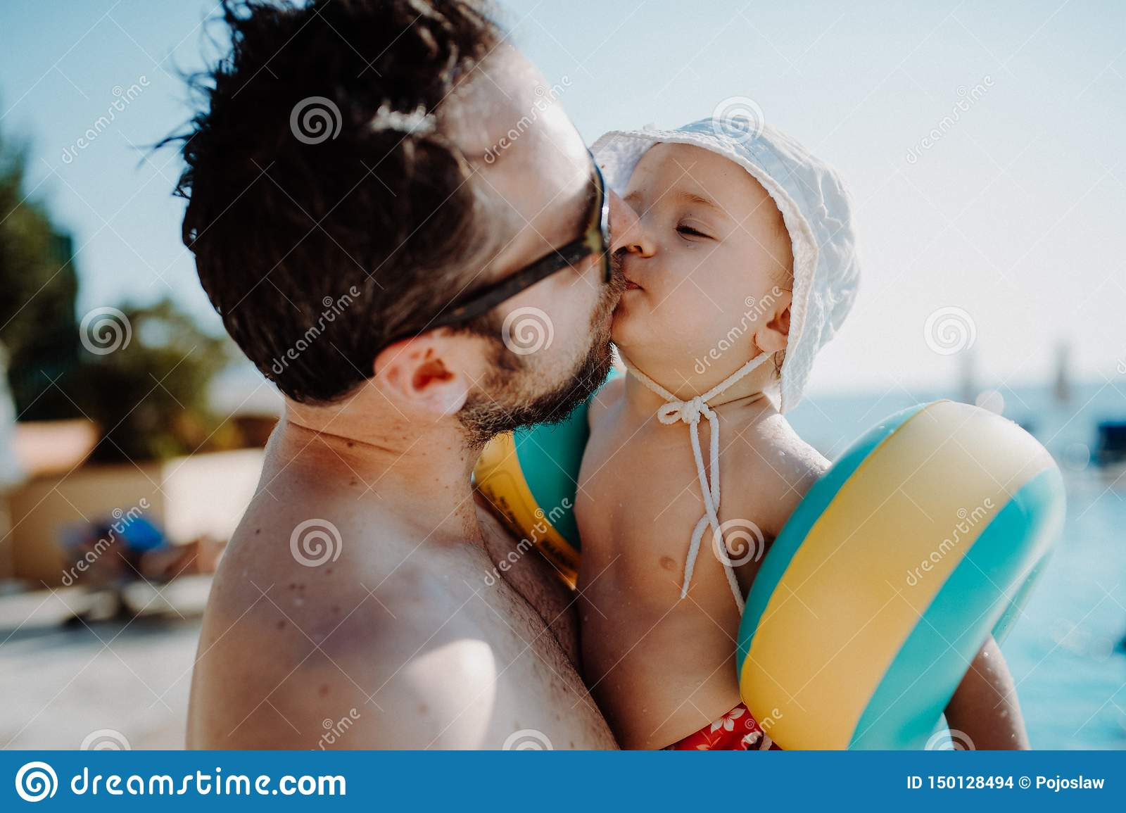 Father with small child with armbands standing by swimming pool on summer holiday.