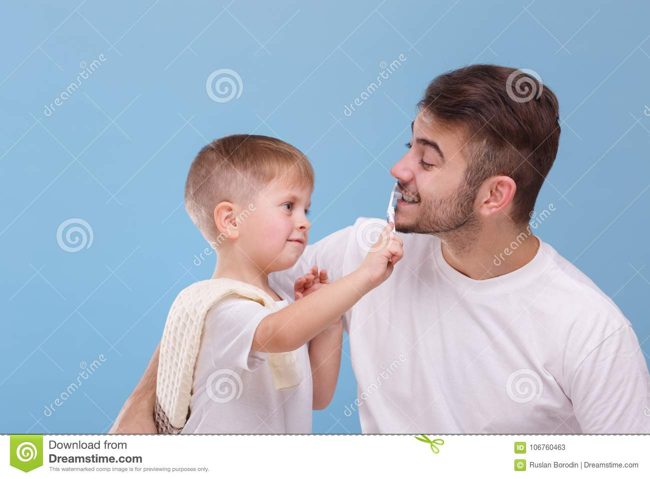 A father with a small son, a small boy will brush his daddy teeth with a toothbrush. On a blue background.