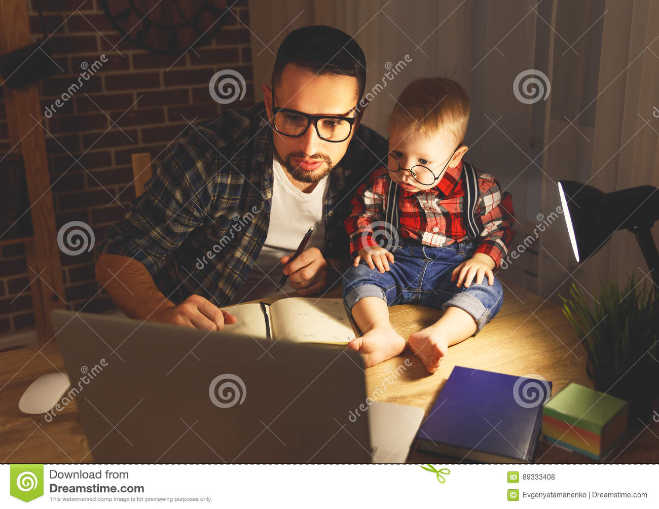 Father and son baby work at home at computer in dark