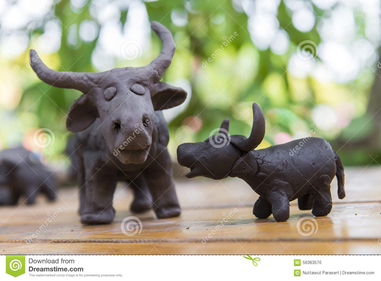 father and son buffalo clay sculpture on wooden background in outdoor