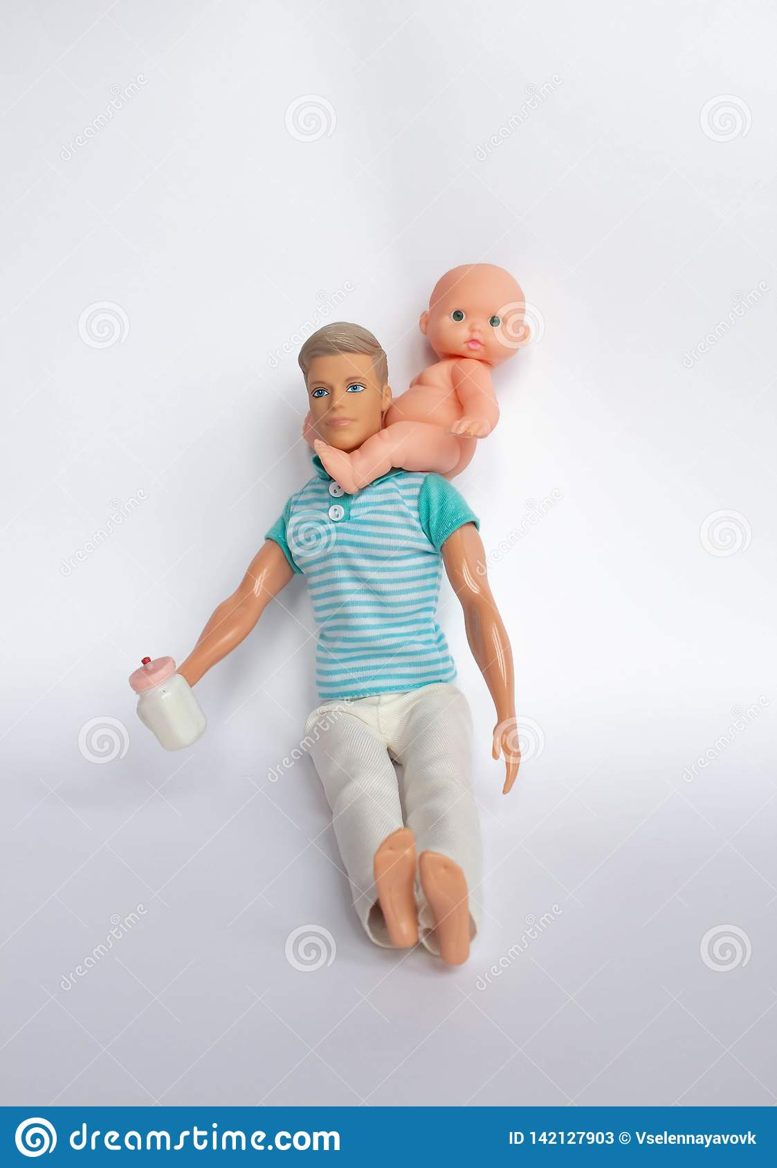 Father and son, dolls on a white background, father holds son in his arms, feeds his son. Caring for the family