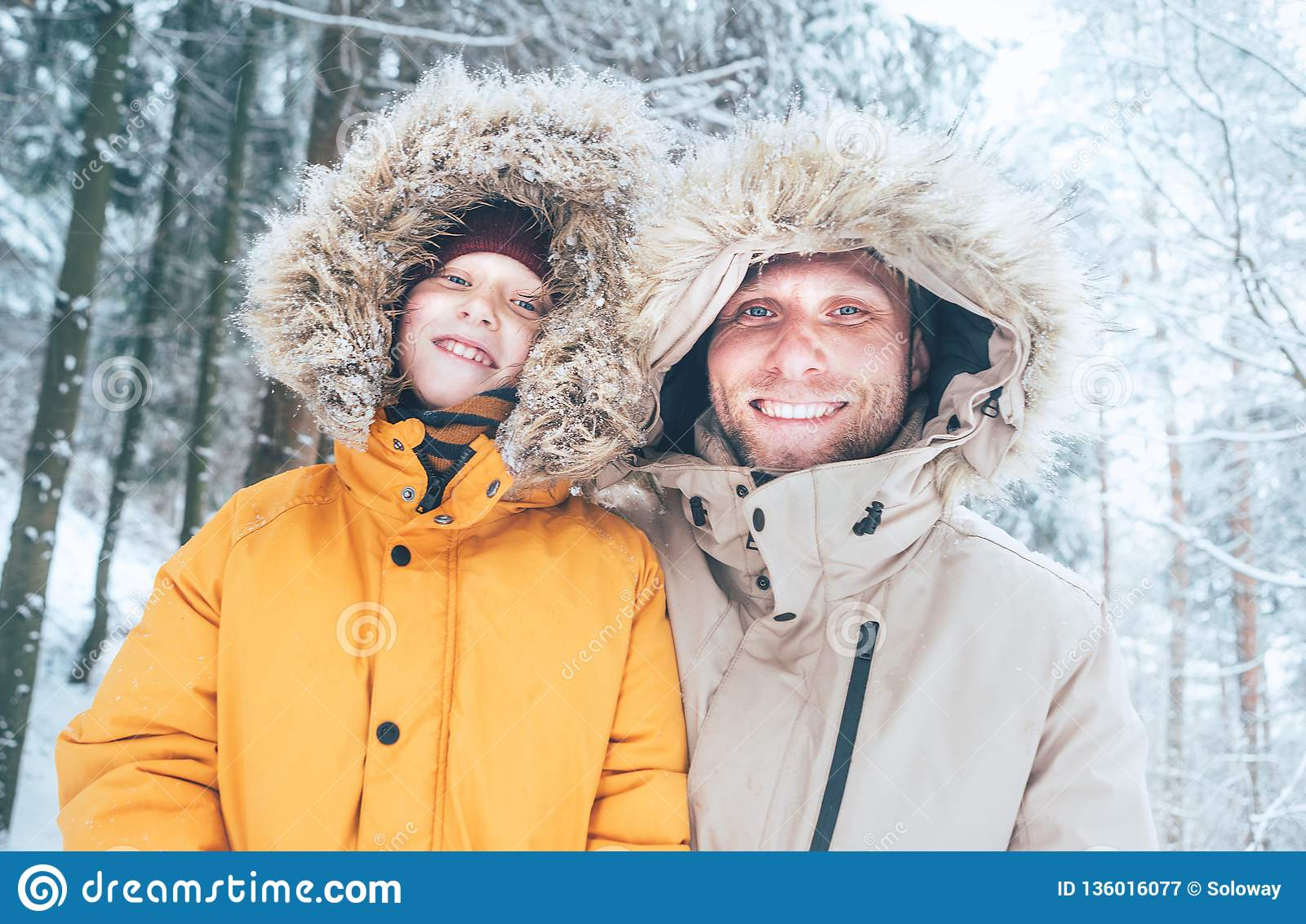 21f5d43bf060c Father and son dressed in Warm Hooded Casual Parka Jacket Outerwear walking  in snowy forest cheerful