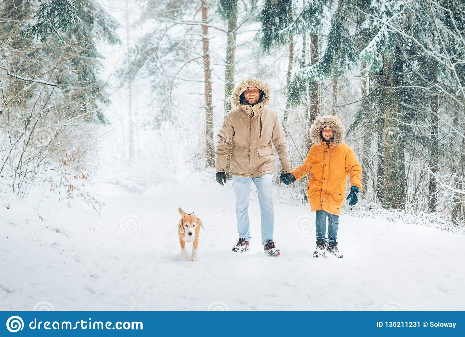 2563d4cb987ea Father and son dressed in Warm Hooded Casual Parka Jacket Outerwear walking  in snowy forest with his beagle dog in pine forest.