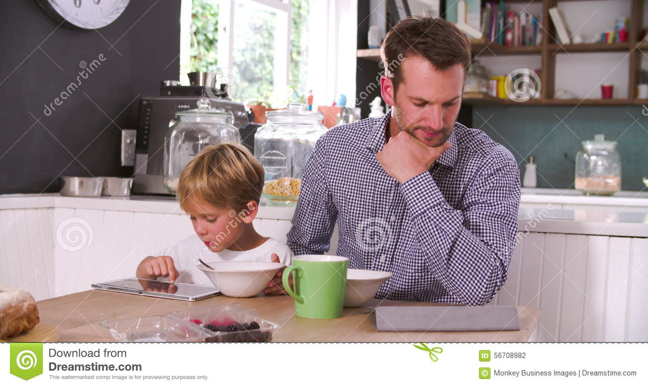 Father And Son Eating Breakfast Whilst Using Digital Tablets Stock ...