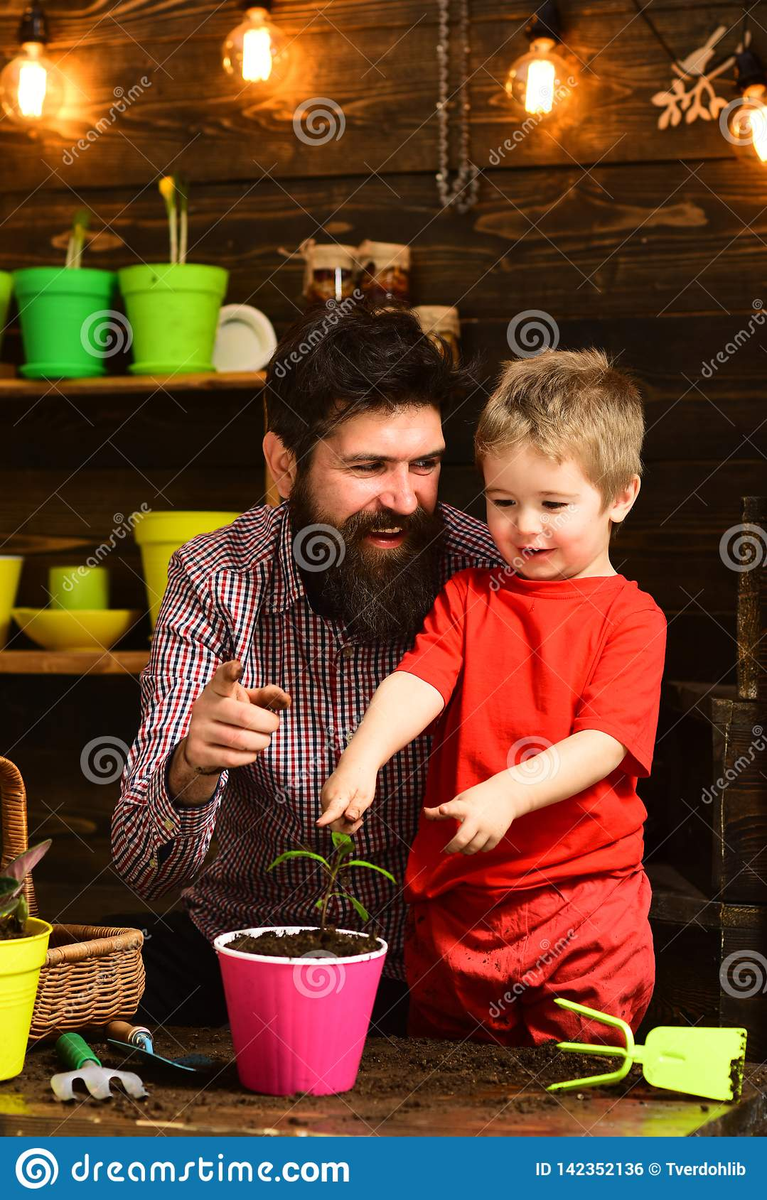 Father and son. Fathers day. Flower care watering. Soil fertilizers. Family day. Greenhouse. bearded man and little boy