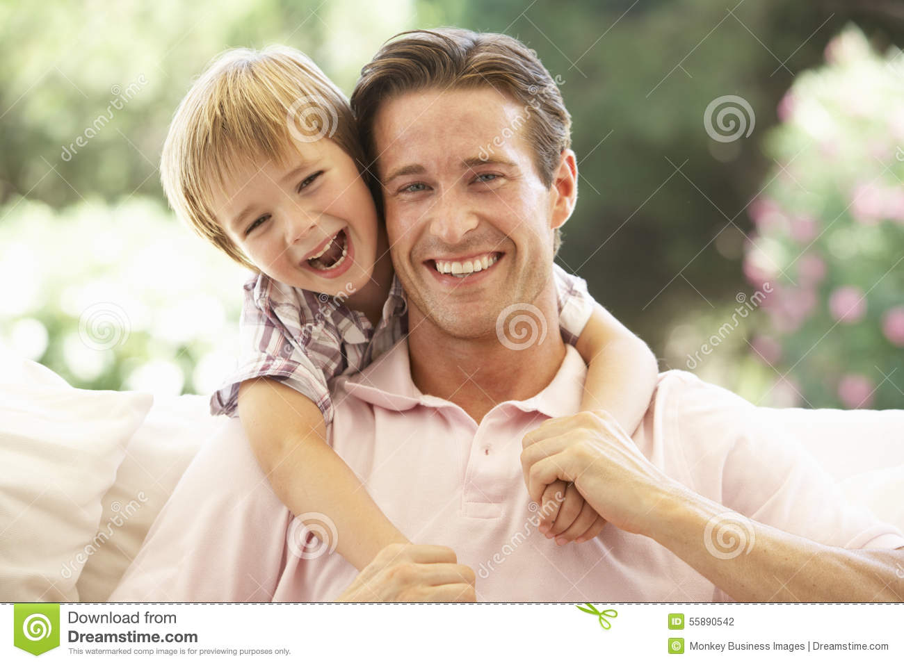 Father With Son Laughing Together On Sofa