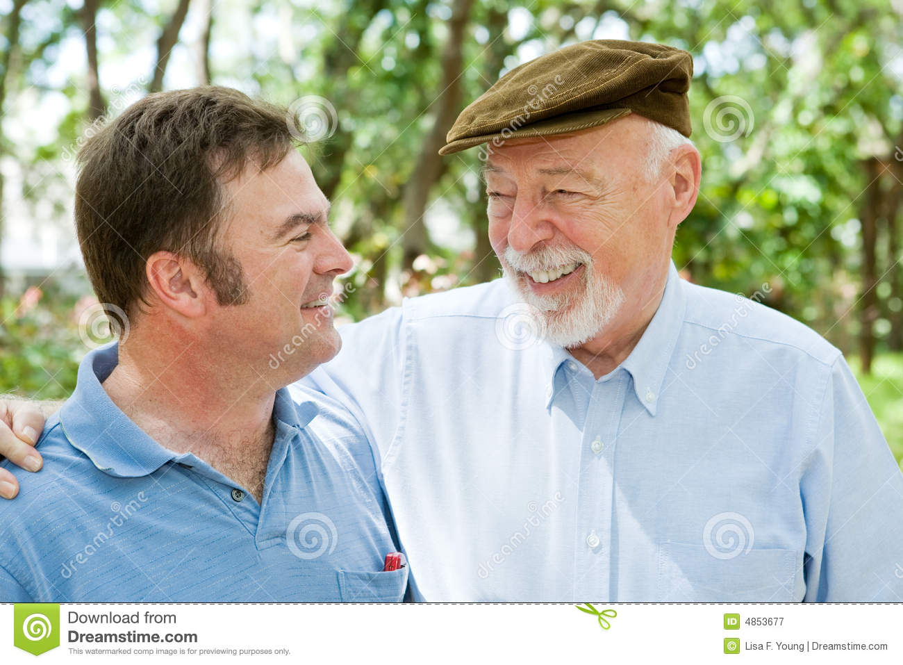 Senior father and adult son laughing together in the park.