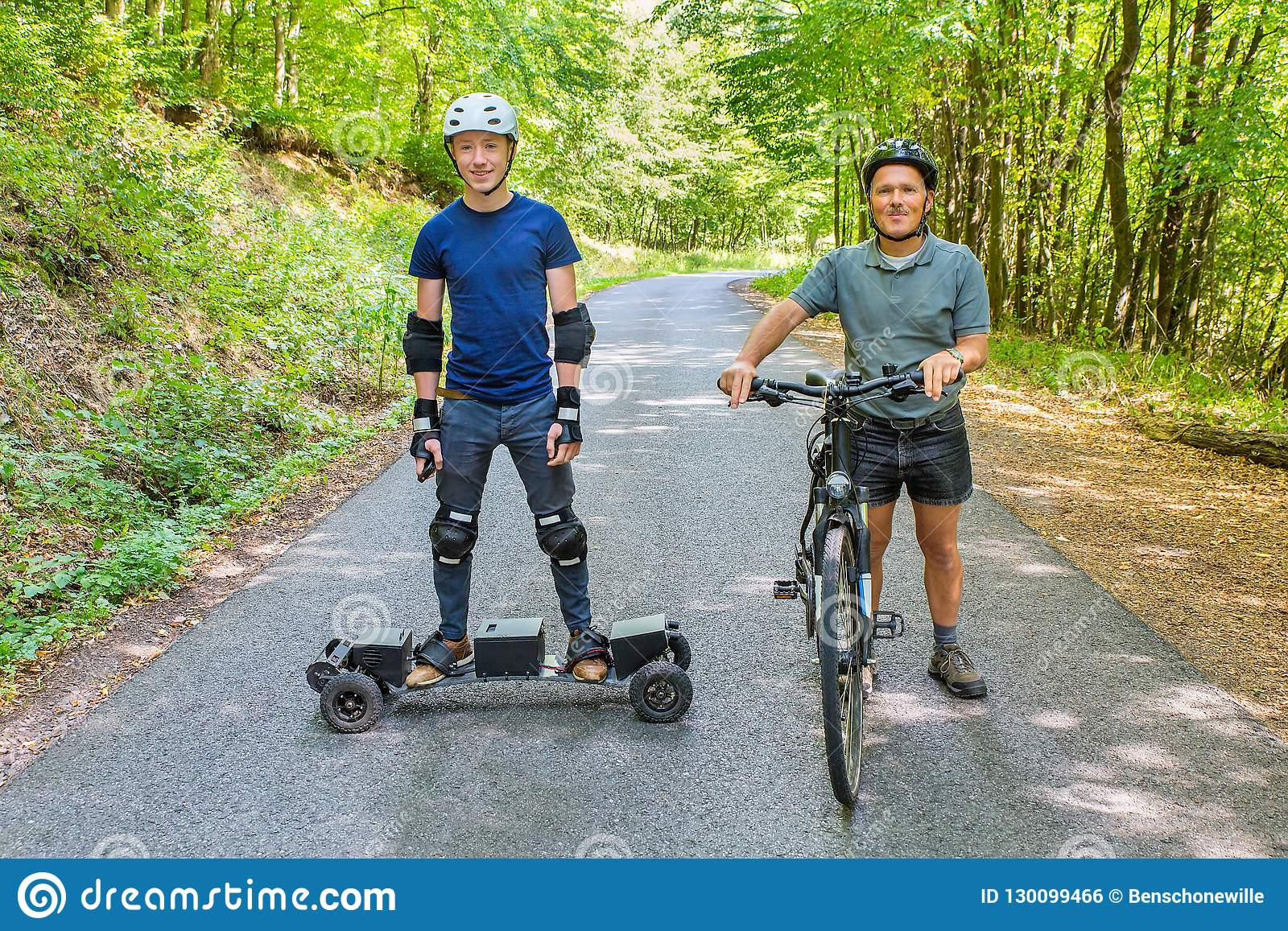 Father and son with mountain bike and mountainboard