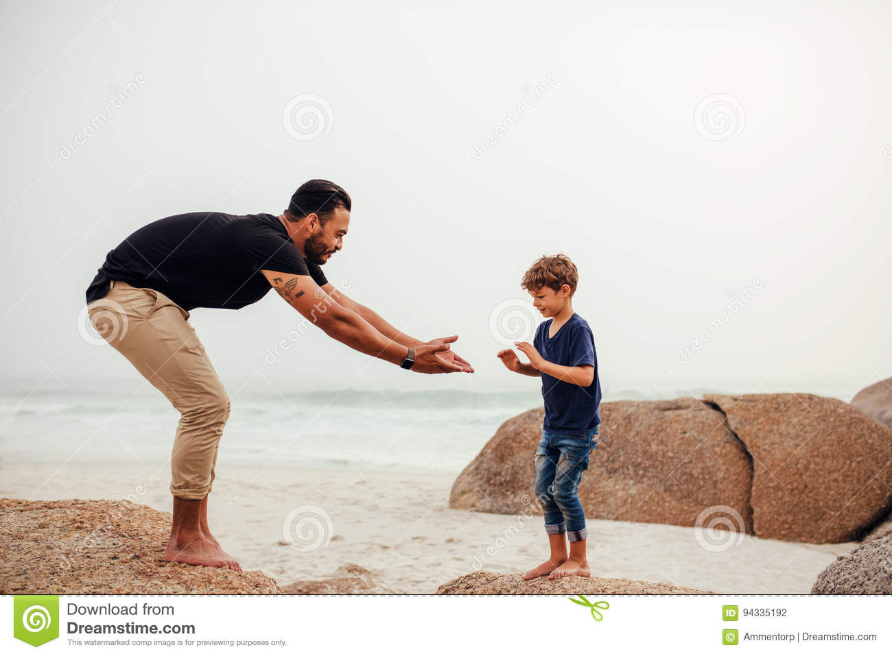 Father and son playing on the rocky beach