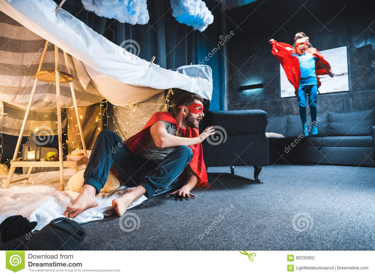 Father and son in red superhero costumes playing
