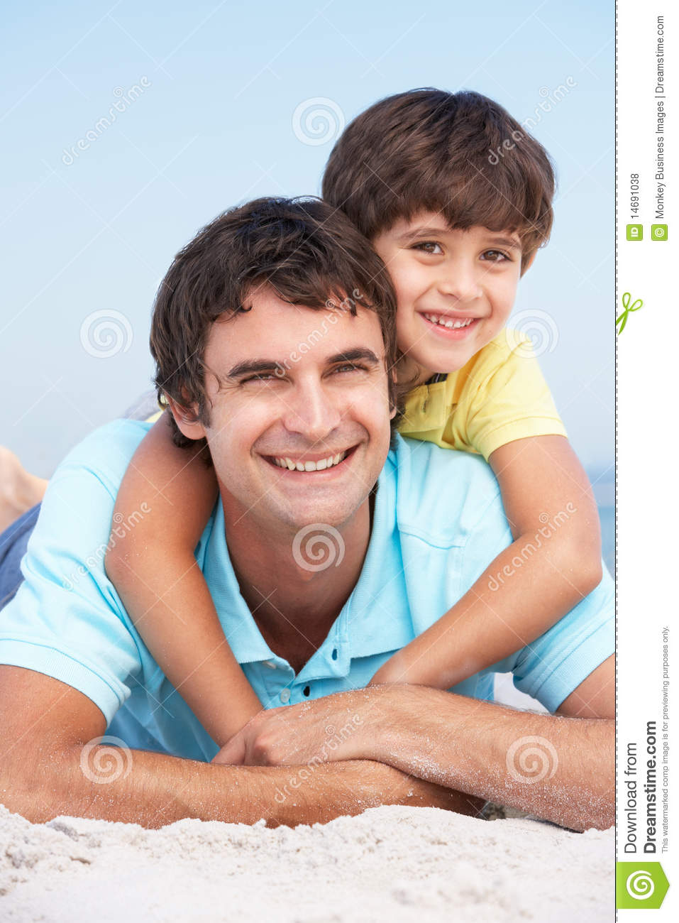 Father And Son Relaxing On Beach Holiday