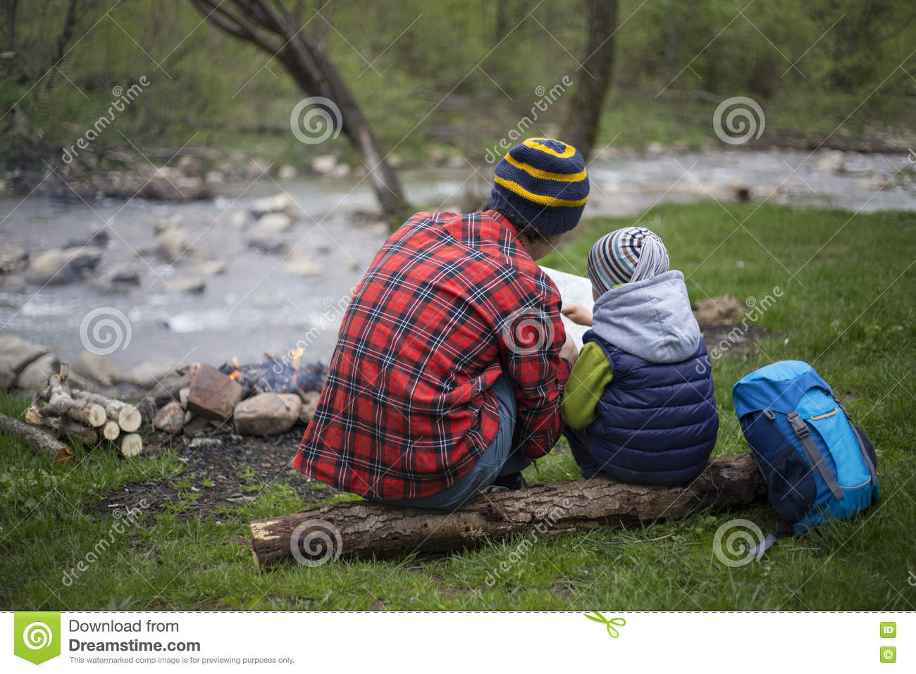 Father and son sitting near a campfire at the campsite and are l