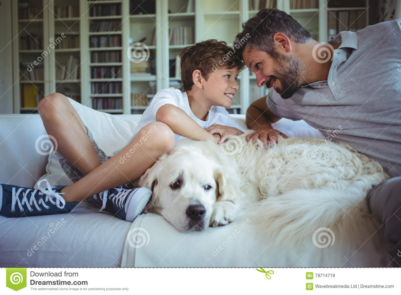 Father And Son Sitting On Sofa With Pet Dog In Living Room Stock