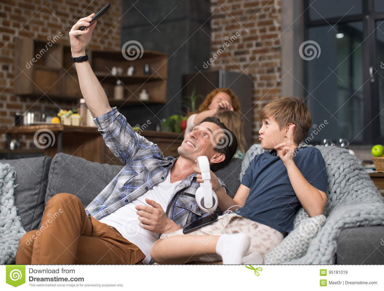 Father And Son Take Selfie Photo On Cell Smart Phone Sitting On Couch In Living Room
