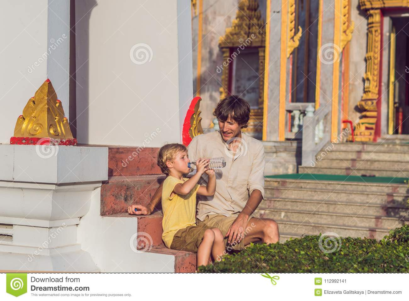 Father and son tourists look at Wat Chalong is the most important temple of Phuket