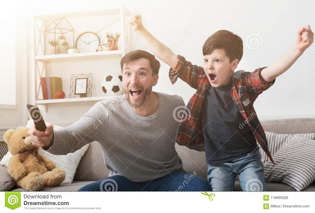 Father and son watching football on TV at home.
