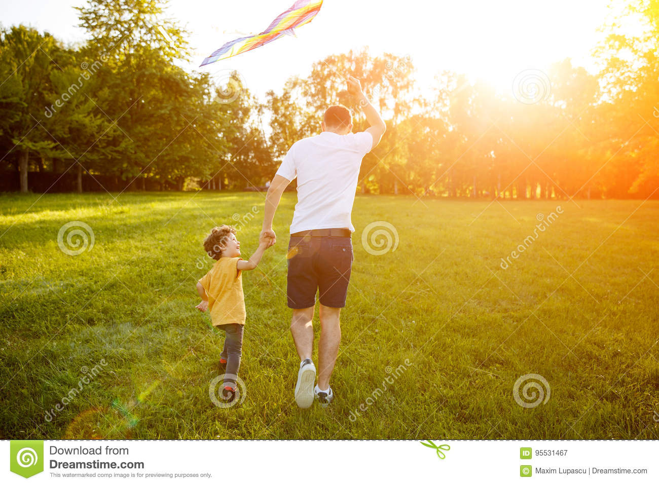 94412016 Father wearing white t-shirt and son dressed in yellow shirt holding hands  launching kite in park running.