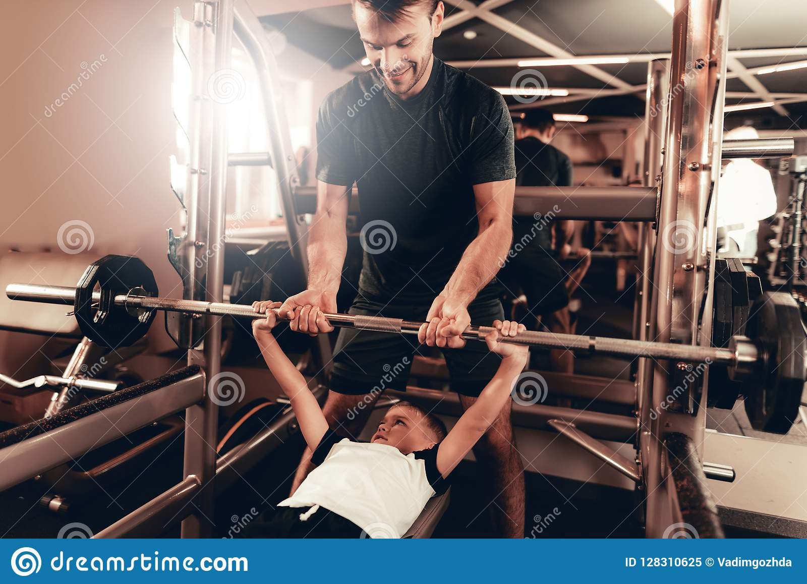 Father Support To Son While Lifting The Barbell.