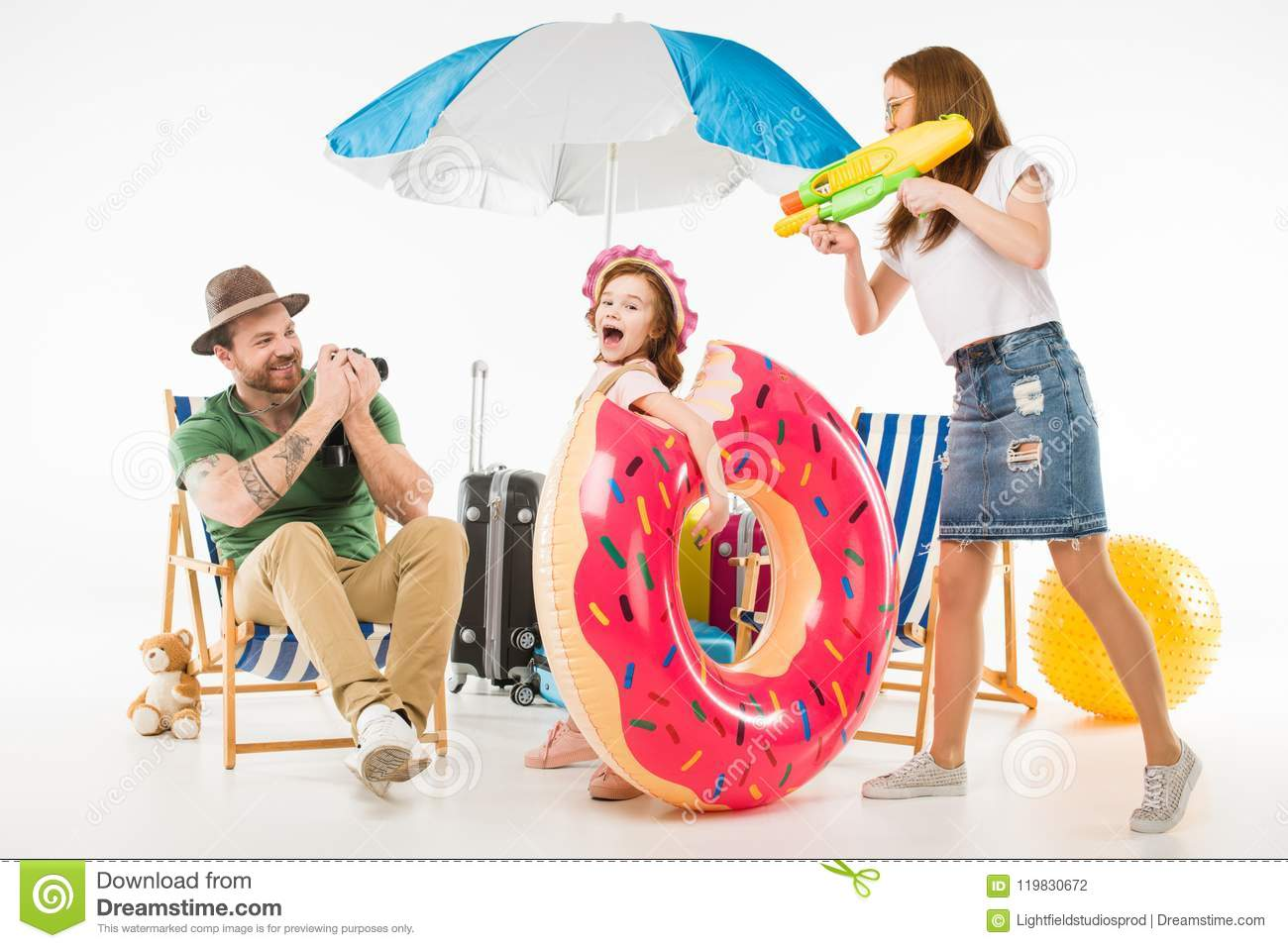 Father taking shot on camera while mother aiming water gun on daughter with flotation ring