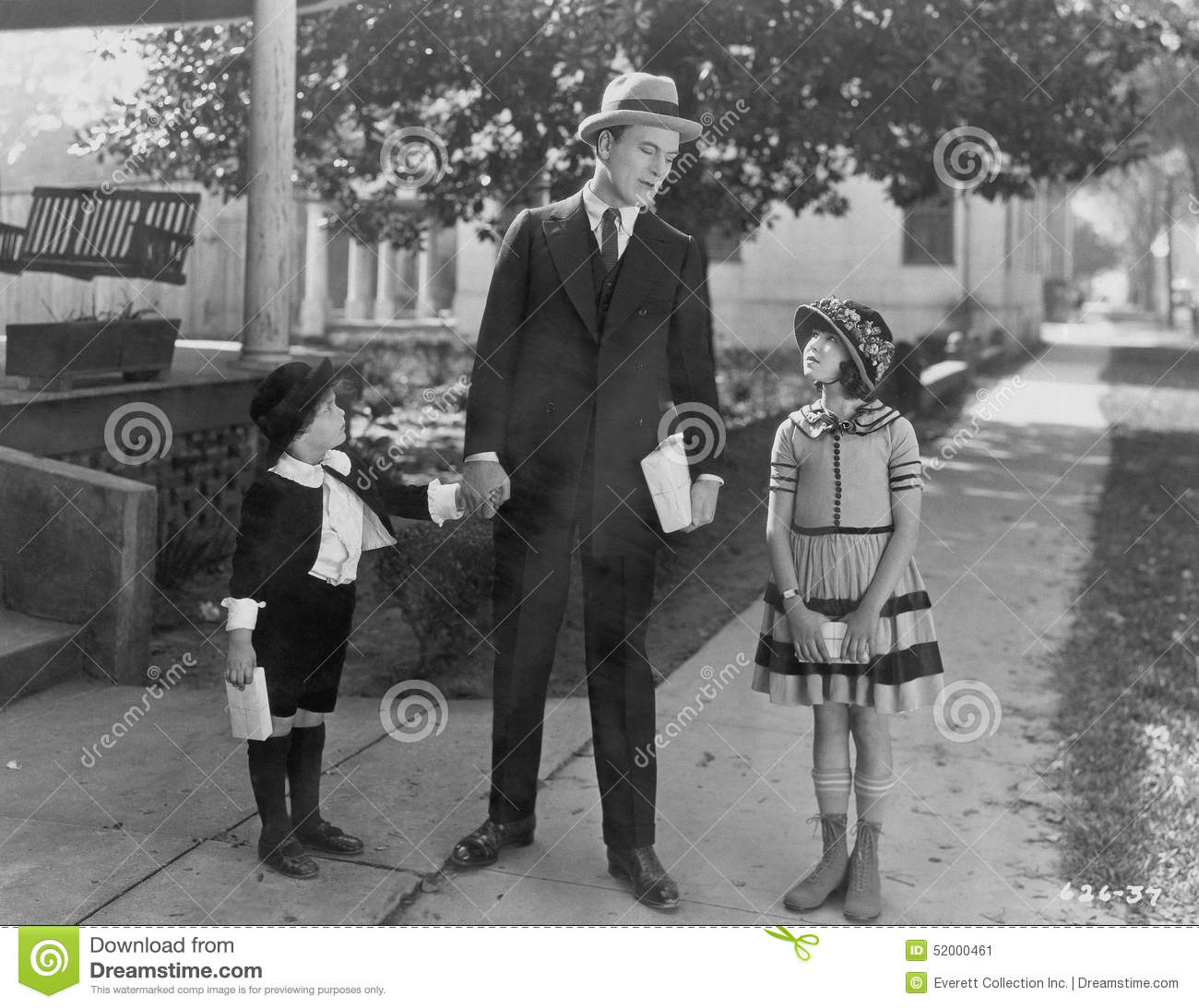 Father talking to two children outside