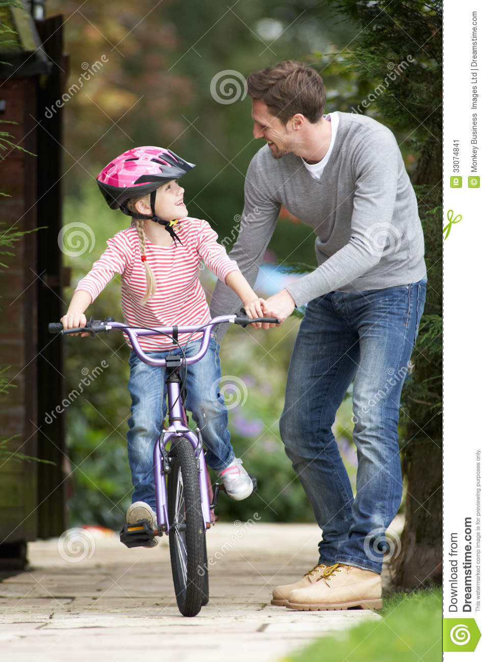 Father Teaching Daughter To Ride Bike In Garden Stock