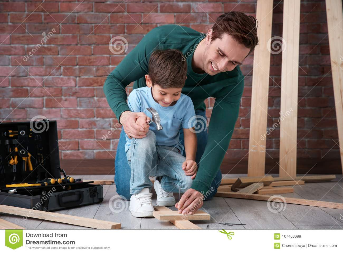 Father teaching his little son to drive nail