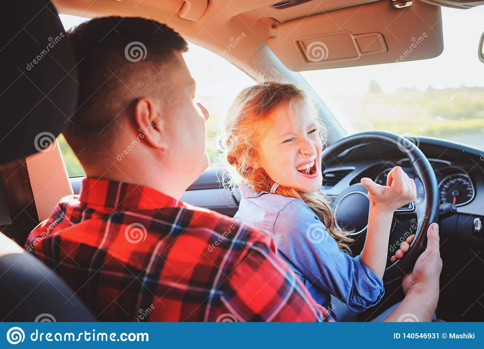 Father teaching kid daughter to drive a car, family traveling