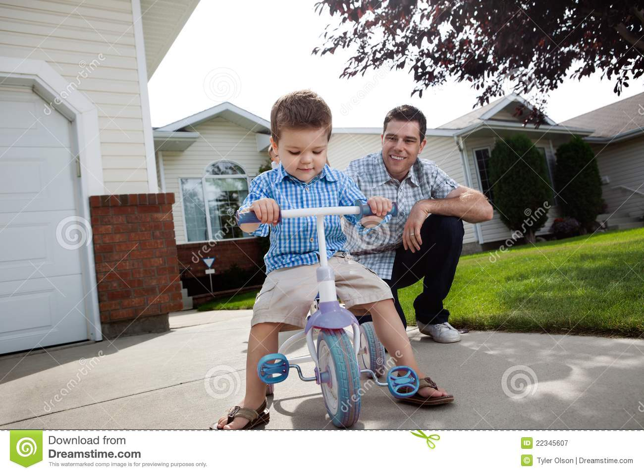 Father teaching Son To Ride a Tricycle