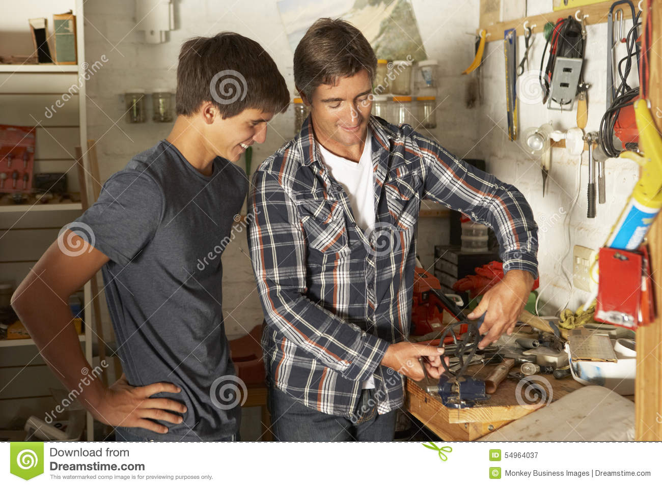 Father Teaching Son To Use Workbench In Garage Stock Image