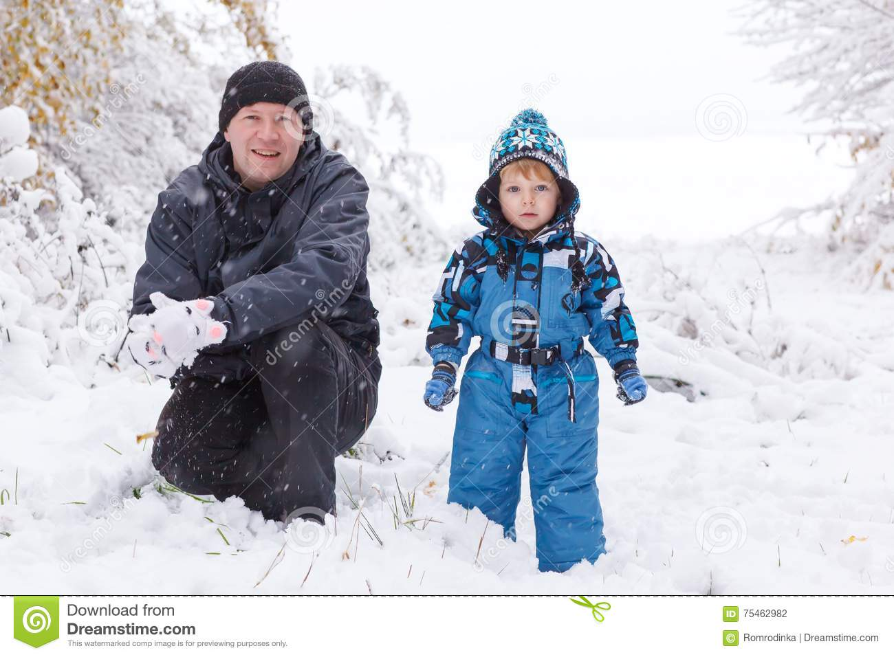 Father and toddler boy having fun with snow on winter day